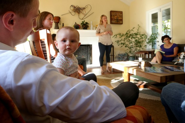 Josephine, Wicks' daughter, looks around from the lap of her father, Peter Ambler, as Wicks speaks during a house party in Oakland. (Ray Chavez/Bay Area News Group)