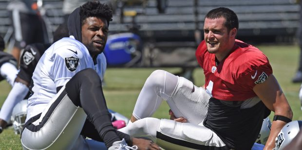 Oakland Raiders' Michael Crabtree (15), left, and quarterback Derek Carr (4) stretch during training camp in Napa, Calif., on Monday, July 31, 2017. (Jose Carlos Fajardo/Bay Area News Group)