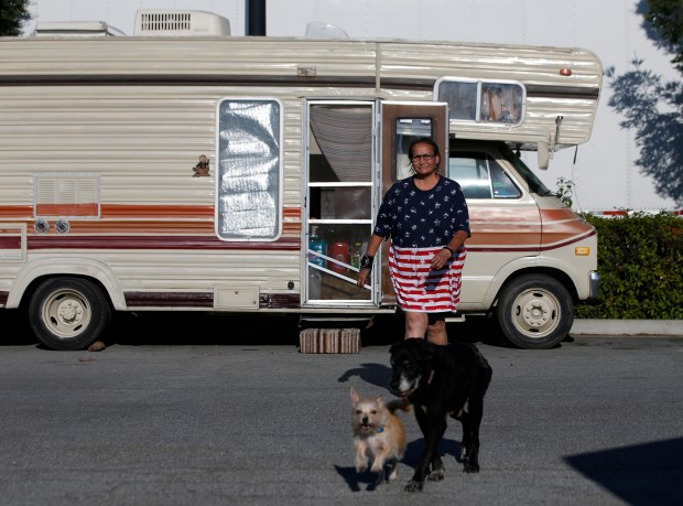 Aida Barron, 58, with her two dogs walks over after moving her 1979 Dodge RV parked on the street near Walmart in Gilroy, Calif. on Monday, July 3, 2017. Aida is a member of the Thousand Trails RV park in Morgan Hill, which is temporarily closed. She is staying at San Benito RV park 21 days and has to move 7 days on to the streets. (Josie Lepe/Bay Area News Group)