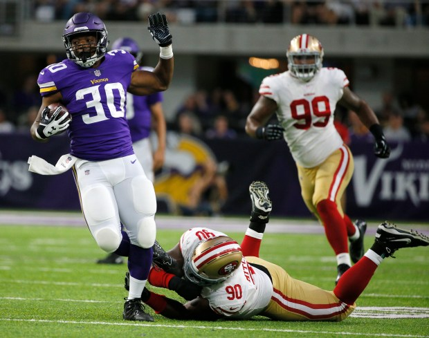 Minnesota Vikings running back C.J. Ham (30) tries to break a tackle by San Francisco 49ers defensive tackle Earl Mitchell (90) during the first half of an NFL preseason football game Sunday, Aug. 27, 2017, in Minneapolis. (AP Photo/Bruce Kluckhohn)