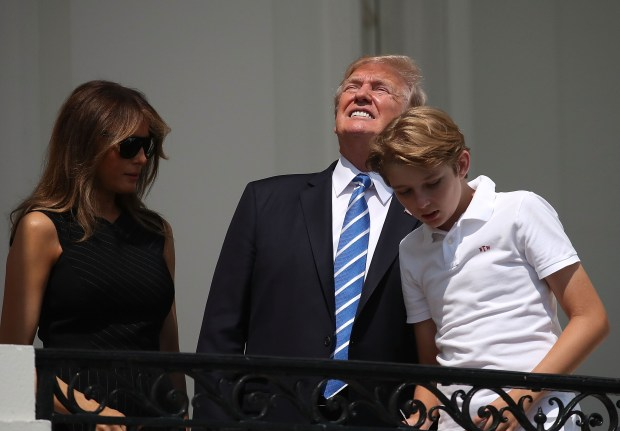 "WASHINGTON, DC - AUGUST 21: (AFP OUT) U.S. President Donald Trump looks up toward the Solar Eclipse while standing with his wife first lady Melania Trump and their son Barron, on the Truman Balcony at the White House on August 21, 2017 in Washington, DC. Millions of people have flocked to areas of the U.S. that are in the ""path of totality"" in order to experience a total solar eclipse. (Photo by Mark Wilson/Getty Images)"