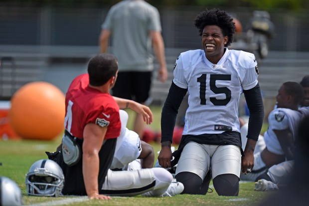 Oakland Raiders wide receiver Michael Crabtree shares a laugh while sitting next to quarterback Derek Carr (4) during training camp in Napa, Calif., on Thursday, August 3, 2017. (Jose Carlos Fajardo/Bay Area News Group)