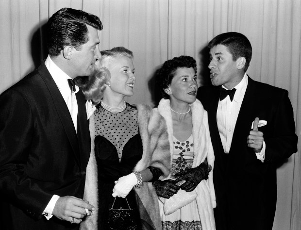 FILE - In a March 29, 1951 file photo, actor-comedian Dean Martin, left, and his wife, Jeanne, are shown with actor-comedian Jerry Lewis, far right, and his wife, singer Patti, as they arrive at the Academy Awards presentations at the RKO Pantages Theatre in Los Angeles. Jerry Lewis, the comedian and director whose fundraising telethons became as famous as his hit movies, died Sunday, Aug. 20, 2017, in Las Vegas, according to his publicist. He was 91. (AP Photo, File)