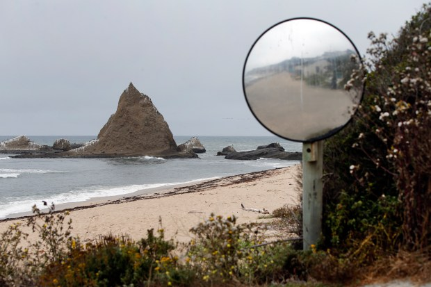 A traffic mirror on the Martins Beach road is covered in salt spray, Tuesday, Aug. 29, 2017, south of Half Moon Bay, California.