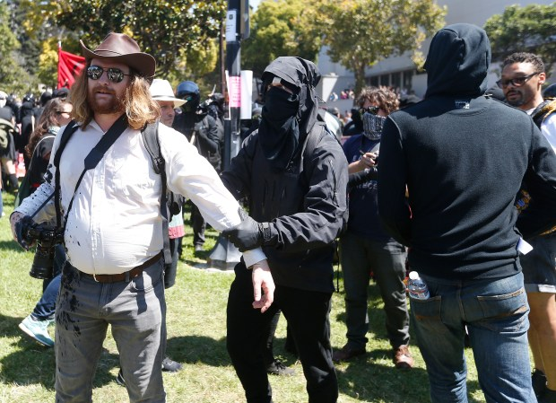 "Protestors grab a man for taking their picture during the ""No to Marxism in America"" rally in Martin Luther King Jr. Civic Center Park on Sunday, Aug.27, 2017, in Berkeley, Calif. (Aric Crabb/Bay Area News Group)"