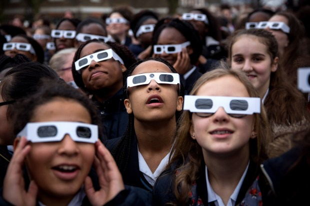 LONDON, UNITED KINGDOM - MARCH 20: Students from Saint Ursula's Covent Secondary School in Greenwich pose for a photograph wearing protective glasses at the Royal Observatory Greenwich on March 20, 2015 in London, England. Hundreds of people gathered outside The Royal Observatory Greenwich hoping see a near total solar eclipse. The solar eclipse, which occurs when the Moon passes between the Sun and the Earth, started at 08:24 GMT and continues until 10:41 GMT, with the maximum obscuration of the Sun happening at 09:31 GMT. The last significant solar eclipse visible from the UK was on 11 August, 1999. (Photo by Rob Stothard/Getty Images)