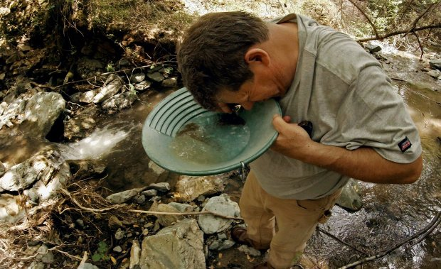 Robert Guardiola of Riverbank uses a magnifying glass to teach for gold inhis pan after collecting gravel deposits under the waterfall on his claim, south of Eagle Creek, on May 15, 2017, near Moccasin, Calif. This year's historic rains and runoff are scouring California's rivers and streams, leaving gold fever in the air. (Gina Ferazzi/Los Angeles Times/TNS)
