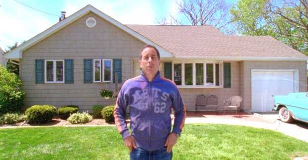 The film shows Seinfeld in various locations from his past, including in front of his childhood home. (Netflix)