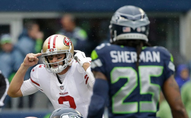 San Francisco 49ers quarterback Brian Hoyer, left, gestures on the line of scrimmage as he lines up against Seattle Seahawks cornerback Richard Sherman (25) in the first half of an NFL football game, Sunday, Sept. 17, 2017, in Seattle. (AP Photo/Elaine Thompson)