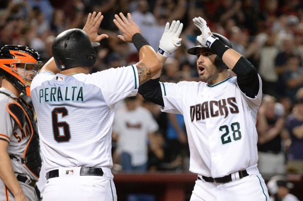 PHOENIX, AZ - SEPTEMBER 26: J.D. Martinez #28 of the Arizona Diamondbacks is congratulated by David Peralta #6 after hitting a grand slam in the second inning of the MLB game against the San Francisco Giants at Chase Field on September 26, 2017 in Phoenix, Arizona. (Photo by Jennifer Stewart/)