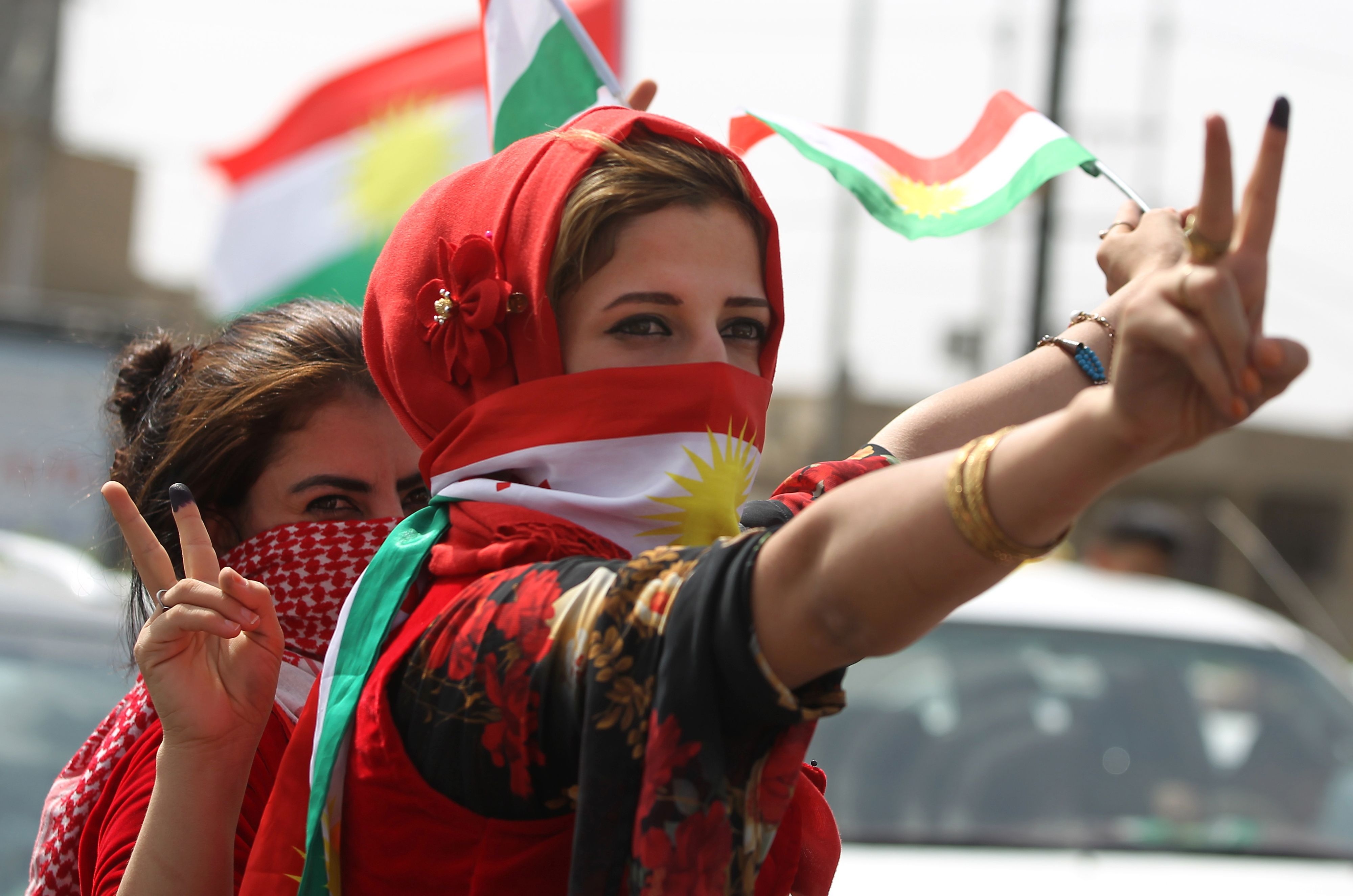 An Iraqi Kurdish woman wearing the Kurdish flag on her face flashes the victory gesture amid celebrations in the city of Kirkuk in northern Iraq, on September 25, 2017 as Iraqi Kurds vote in a referendum on independence.The non-binding vote, initiated by veteran Kurdish leader Massud Barzani, has angered not only Baghdad, following which Iraq's federal parliament demanded that troops be sent to disputed areas in the north controlled by the Kurds since 2003, but also neighbours Turkey and Iran who are concerned it could stoke separatist aspirations among their own sizeable Kurdish minorities. / AFP PHOTO / AHMAD AL-RUBAYEAHMAD AL-RUBAYE/AFP/Getty Images