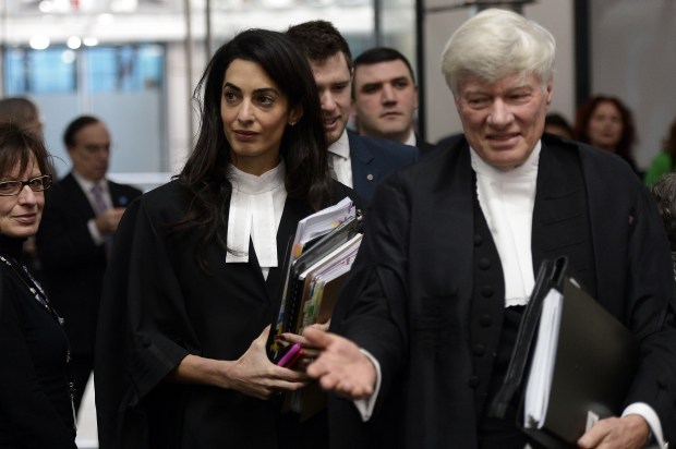 Lawyers representing Armenia, Amal Clooney (L) and Geoffrey Robertson, arrive on January 28, 2015 to attend the appeal hearing in Perincek case before the European Court of Human Rights in the eastern French city of the Strasbourg. Turkish politician Dogu Perincek from the Left-wing Turkish Workers Party, was found guilty by a Swiss court in 2008 of denying, during a visit to Switzerland, that the 1915 genocide, in which up to 1.5 million Armenians were slaughtered, ever took place. Perincek was fined by a court in Switzerland. He appealed to the European Court of Human Rights in Strasbourg, which ruled in Dec 2013 that Switzerland had violated his right to free expression. His appeal is now being challenged by Armenia. AFP PHOTO / FREDERICK FLORIN (Photo credit should read FREDERICK FLORIN/AFP/Getty Images)