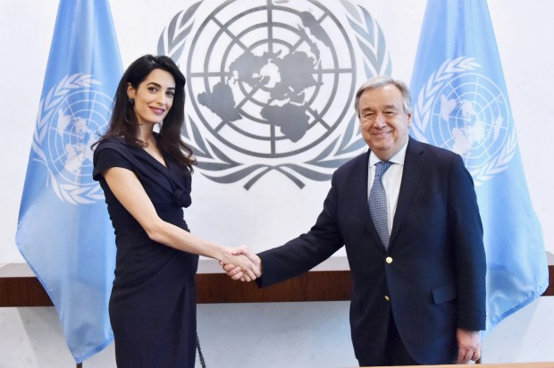 NEW YORK, NY - MARCH 10: International Human Rights Lawyer Amal Clooney (L) and 9th Secretary-General of the United Nations António Guterres shake hands at United Nations Headquarters on March 10, 2017 in New York City. (Photo by Mike Coppola/Getty Images)