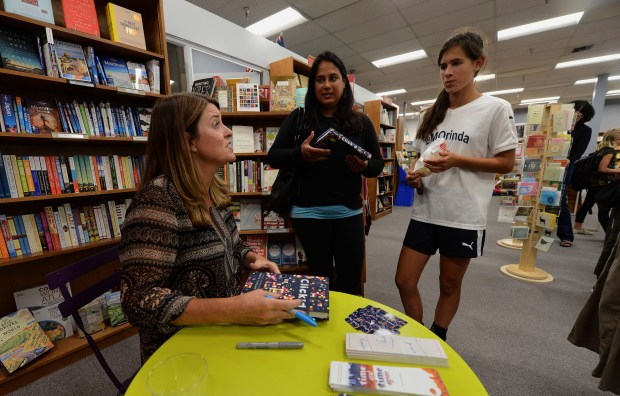 Local author Tamara Ireland Stone, left, signs books as she chats with Toinette, center, and Maddy Reynolds, of Orinda, at a special book launch event at Orinda Books in Orinda, Calif., on Thursday, Sept. 7, 2017. Independent bookstores have a new competitor in the form of brick-and-mortar Amazon bookstores opening up around the Bay Area. Orinda Books tries to attract customers by offering special events. (Dan Honda/Bay Area News Group)