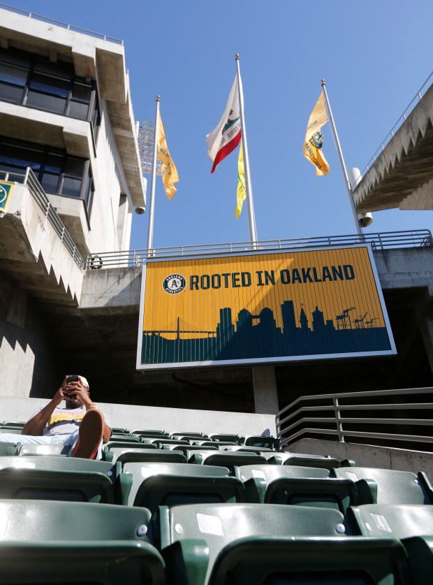 A game attendee relaxes under the sign near the bleacher seats during the last A's home game of the season at the Oakland-Alameda Coliseum in Oakland Calif., on Wednesday, Sept. 27, 2017. (Laura A. Oda/Bay Area News Group)