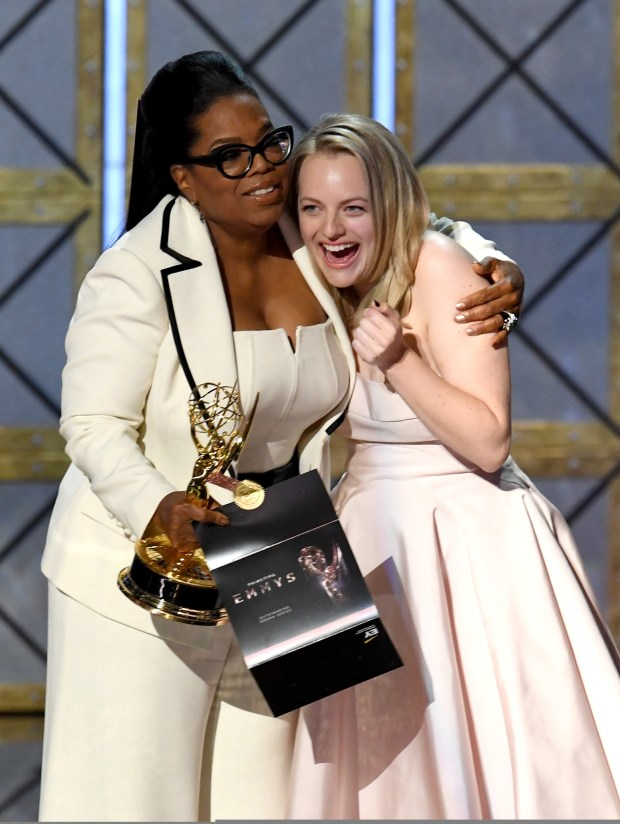 LOS ANGELES, CA - SEPTEMBER 17: Actor Elisabeth Moss (R) accepts Outstanding Drama Series for 'The Handmaid's Tale' from Oprah Winfrey onstage during the 69th Annual Primetime Emmy Awards at Microsoft Theater on September 17, 2017 in Los Angeles, California. (Photo by Kevin Winter/Getty Images)