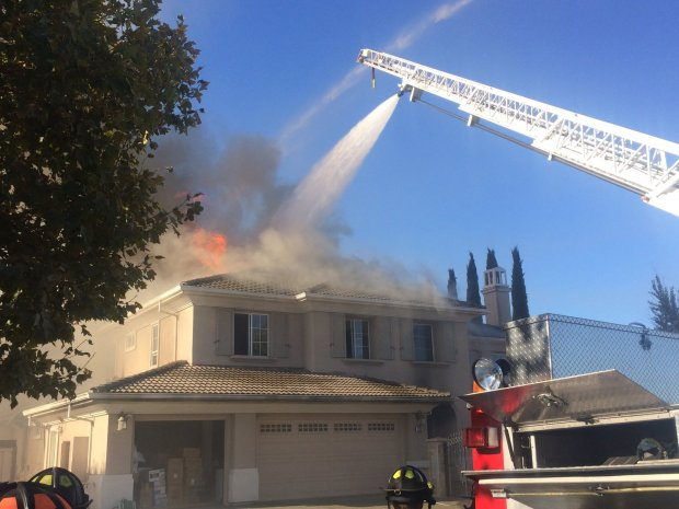 San Jose Fire Department personnel work to extinguish a two-alarm fire at a home on Chisin Street in the Evergreen area on Sept. 26, 2017.