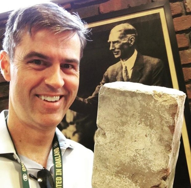 As a salute to their past, the A's imported bricks from their previous homeof Shibe Park in Philadelphia. Reporter Daniel Brown holds one here while standing in front of a portrait of Connie Mack, who helped design the park. (Courtesy photo)