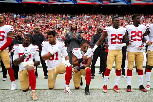 LANDOVER, MD - OCTOBER 15: K'Waun Williams #24, Arik Armstead #91 and Eli Harold #57 of the San Francisco 49ers kneel while holding their hands over their chest during the U.S. national anthem before playing against the Washington Redskins at FedExField on October 15, 2017 in Landover, Maryland. (Photo by Patrick Smith/Getty Images) *** BESTPIX ***