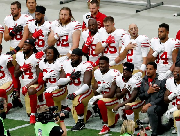 Members of the San Francisco 49ers kneel during the national anthem as others stand prior to an NFL football game against the Arizona Cardinals, Sunday, Oct. 1, 2017, in Glendale, Ariz. (AP Photo/Matt York)