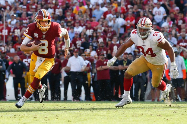 Washington Redskins quarterback Kirk Cousins (8) carries the ball toward the end zone a touchdown as San Francisco 49ers defensive end Solomon Thomas (94) looks on during the second half of an NFL football game in Landover, Md., Sunday, Oct. 15, 2017. (AP Photo/Alex Brandon)