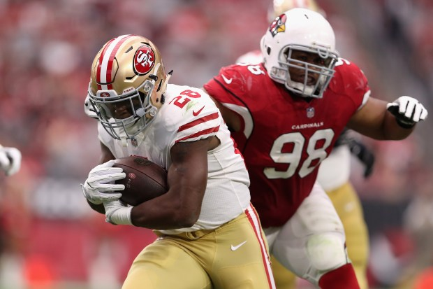 Running back Carlos Hyde #28 of the San Francisco 49ers slips past nose tackle Corey Peters #98 of the Arizona Cardinals during the second half of the NFL game at the University of Phoenix Stadium on October 1, 2017 in Glendale, Arizona. (Photo by Christian Petersen/Getty Images)