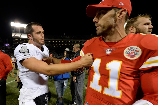 Oakland Raiders quarterback Derek Carr (4) shares words with Kansas City Chiefs quarterback Alex Smith (11) after winning their NFL game at the Coliseum in Oakland, Calif. on Thursday, Oct. 19, 2017. Oakland defeated Kansas City 31-30. (Jose Carlos Fajardo/Bay Area News Group)