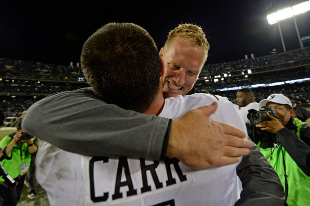 Oakland Raiders quarterback coach Todd Downing hugs Oakland Raiders quarterback Derek Carr (4) as they celebrate their win against the Kansas City Chiefs during their NFL game at the Coliseum in Oakland, Calif. on Thursday, Oct. 19, 2017. Oakland defeated Kansas City 31-30. (Jose Carlos Fajardo/Bay Area News Group)