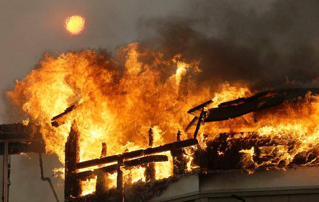 The sun shines above behind a burning building at the Hilton Sonoma Wine Country hotel in Santa Rosa, Calif., Monday, Oct. 9, 2017. Wildfires whipped by powerful winds swept through Northern California sending residents on a headlong flight to safety through smoke and flames as homes burned. (AP Photo/Jeff Chiu)