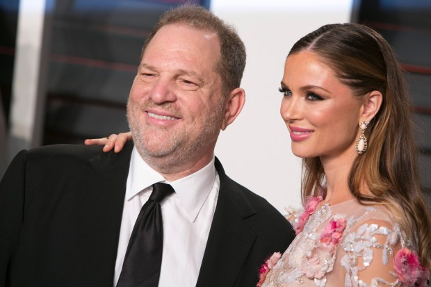 US producer Harvey Weinstein poses with his wife Georgina Chapman as they arrive to the 2016 Vanity Fair Oscar Party in Beverly Hills, California on February 28, 2016. / AFP / ADRIAN SANCHEZ-GONZALEZ (Photo credit should read ADRIAN SANCHEZ-GONZALEZ/AFP/Getty Images)