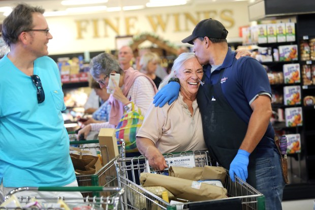 Saratoga resident Marilyn Bierach gets a hug and kiss from Gene's Fine Food's Produce Manager Chris Bonton, who has been working at the store for 25 years. Bierach, who has been a loyal customer since Gene's opened 47 years ago, is heartbroken that the store will be closing for good. (George Sakkestad/Staff Photographer)