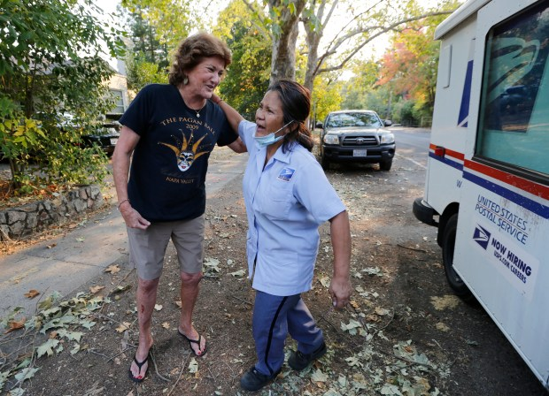 The two Connies, Connie Taylor, left, and Connie Gumataotao were so happy to see each other as Gumataotao delivers mail for the first time since the evacuation in Calistoga, Calif, on Monday, Oct. 16, 2017. After the evacuation order was lifted for the town of Calistoga ,residents and businesses begin trying to get back to normal. (Laura A. Oda/Bay Area News Group)