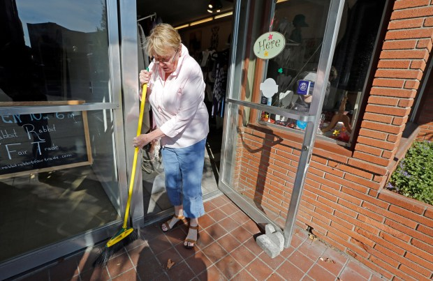Carol Bush sweeps ash from the front of her woman's clothing store Northstar as she opens for customers in the business district of Calistoga, Calif, on Monday, Oct. 16, 2017. After the evacuation order was lifted for the town of Calistoga ,residents and businesses begin trying to get back to normal. (Laura A. Oda/Bay Area News Group)