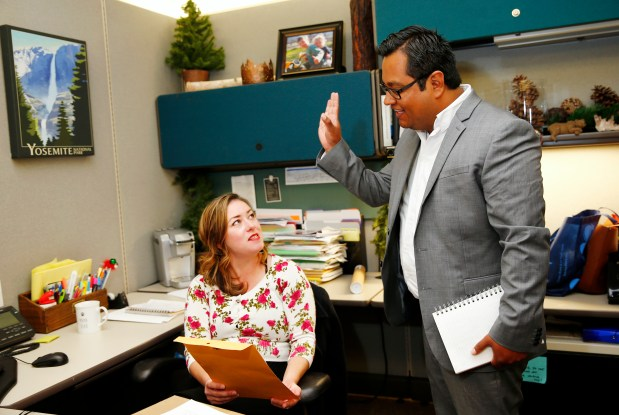 Mario Lopez, right, works with Vanessa Turner, both policy aides to Santa Clara County Supervisor Dave Cortese, at their office in San Jose, California, on Thursday, Oct. 12, 2017. Lopez, 30, of San Jose, is a DACA recipient. He helped start a fellowship program that provides paid internships in county government to undocumented youth. (Gary Reyes/ Bay Area News Group)