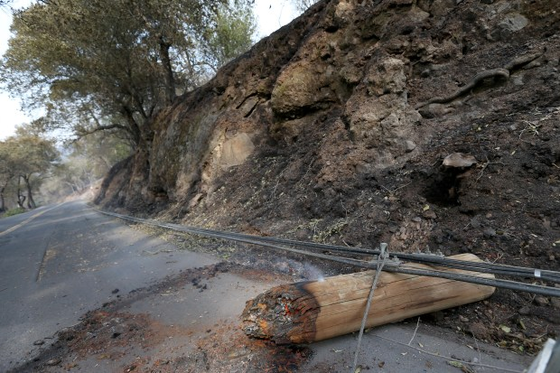 Downed power poles burn along Soda Canyon Road in Napa, Calif., on Tuesday, Oct. 10, 2017. Power was out around a large portion of the area. (Jane Tyska/Bay Area News Group)