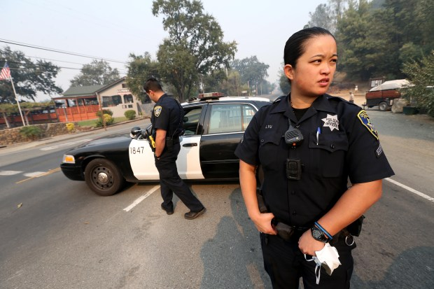 Oakland police officers Julie Yu, right, and Matt Shahnazari monitor a checkpoint at the intersection of Lincoln Avenue and Lake Street in Calistoga, Calif., on Wednesday, Oct. 11, 2017. Half of Calistoga was evacuated due to an approaching fire coming from the east. (Jane Tyska/Bay Area News Group)