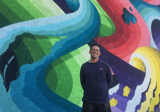 Artist Ricky Watts stands in front of his mural in progress in downtown SanJose for the Pow! Wow! San Jose festival. (Sal Pizarro/Bay Area News Group)