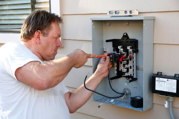 Paul Nijssen of EVcharge4U installs a new electrical panel for an electric vehicle charger in a home in Alamo, California, on Thursday, Oct. 26, 2017. Nijssen is the co-founder of EVcharge4U. (Gary Reyes/ Bay Area News Group)