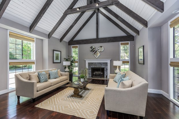 The spacious formal living room features a fireplace with granite surround and a vaulted ceiling with exposed beams.