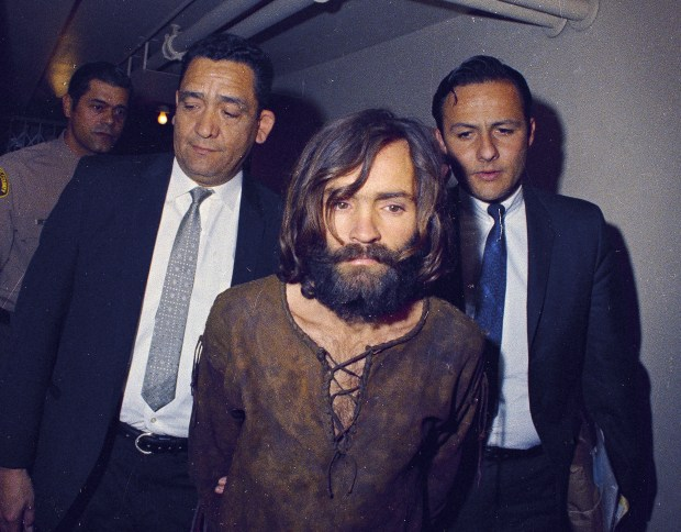 Charles Manson is escorted to his arraignment on conspiracy-murder charges in conneciton with the Sharon Tate murder case, 1969, Los Angeles, Calif. (AP Photo)