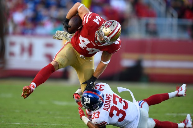 San Francisco 49ers' Kyle Juszczyk (44) runs with the ball and is tackled by New York Giants' Andrew Adams (33) during the third quarter of their NFL game at Levi's Stadium in Santa Clara, Calif., on Sunday, Nov. 12, 2017. San Francisco defeated New York 31-21. (Jose Carlos Fajardo/Bay Area News Group)