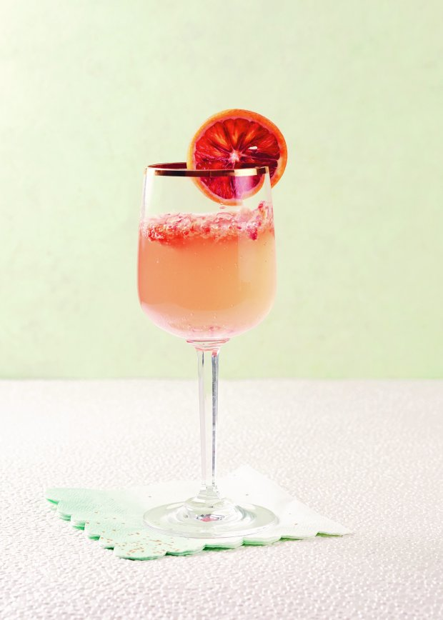 "The Blood Orange Sparkler, from Nick Mautone's ""Holiday Cocktails,"" offers a celebratory sip of winter citrus, served in a festive stem. (Photo:Lauren Volo)"