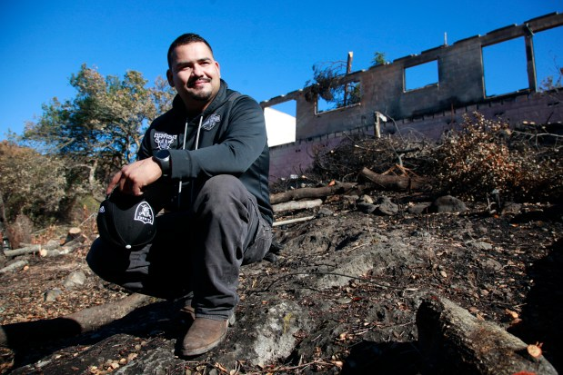 Sam Valencia takes a break while clearing debris from his employer's property destroyed in the Atlas Peak fire on Tuesday, November 14, 2017. Valencia woke up his boss Dave Melnick, saving his life as the Wine Country fires roared down the mountain. (Karl Mondon/Bay Area News Group)