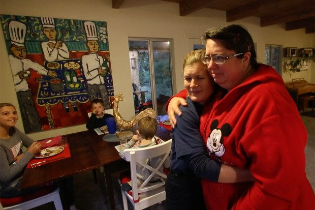 Caroline Upton and Michelle Hickman hug Wednesday morning, while their two families share the breakfast table Wednesday morning, November 15, 2017, at Upton's home in Calistoga, California. Hickman, a neighbor, lost her home in the Tubbs fire last month, and Upton, a volunteer firefighter, and her family have befriended the Hickman's to help provide her children some normalcy. (Karl Mondon/Bay Area News Group)