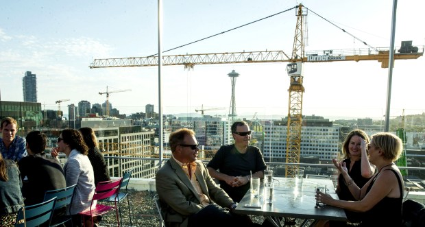 Chris OíConnor, center, closest to camera wearing sunglasses, Glen Snyder, Laura Taylor, brunette, and Maggie Snyder talk at Mbar in Seattleís South Lake Union neighborhood. The group members were talking about the number of cranes in the skyline. Mamnoonís Wassef and Racha Haroun own the restaurant.