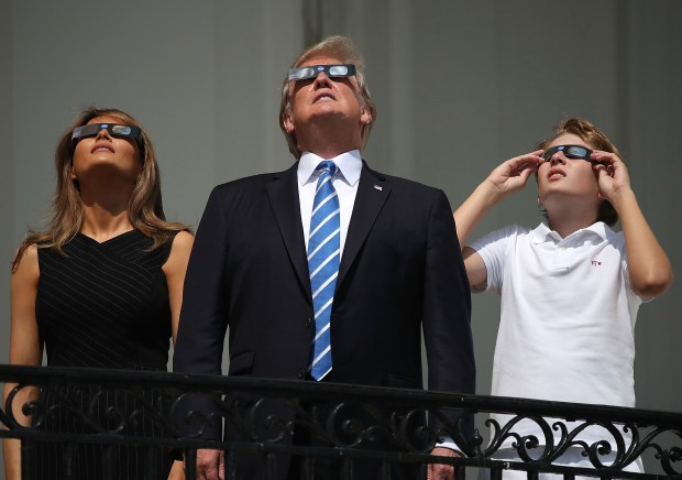 "WASHINGTON, DC - AUGUST 21: (One of a 115-image Best of Year 2017 set) (AFP OUT) U.S. President Donald Trump, first lady Melania Trump and their son Barron Trump wear special glasses to view the solar eclipse from the Truman Balcony at the White House on August 21, 2017 in Washington, DC. Millions of people have flocked to areas of the U.S. that are in the ""path of totality"" in order to experience a total solar eclipse. (Photo by Mark Wilson/Getty Images)"