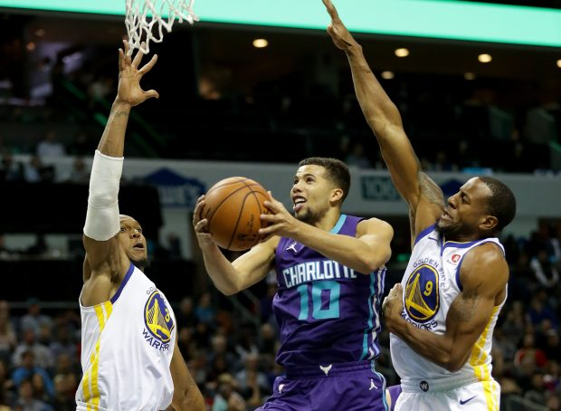 CHARLOTTE, NC - DECEMBER 06: Michael Carter-Williams #10 of the Charlotte Hornets drives to the basket against teammates David West #3 and Andre Iguodala #9 of the Golden State Warriors during their game at Spectrum Center on December 6, 2017 in Charlotte, North Carolina. NOTE TO USER: User expressly acknowledges and agrees that, by downloading and or using this photograph, User is consenting to the terms and conditions of the Getty Images License Agreement. (Photo by Streeter Lecka/Getty Images)