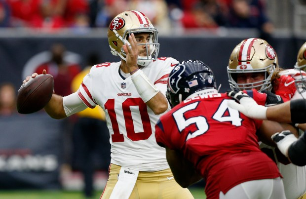 HOUSTON, TX - DECEMBER 10: Jimmy Garoppolo #10 of the San Francisco 49ers throws a pass as LaTroy Lewis #54 of the Houston Texans applies pressure at NRG Stadium on December 10, 2017 in Houston, Texas. (Photo by Bob Levey/Getty Images)