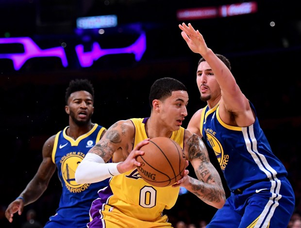 LOS ANGELES, CA - DECEMBER 18: Kyle Kuzma #0 of the Los Angeles Lakers drives on Klay Thompson #11 and Jordan Bell #2 during a 116-114 Warrior overtime win at Staples Center on December 18, 2017 in Los Angeles, California. (Photo by Harry How/Getty Images)