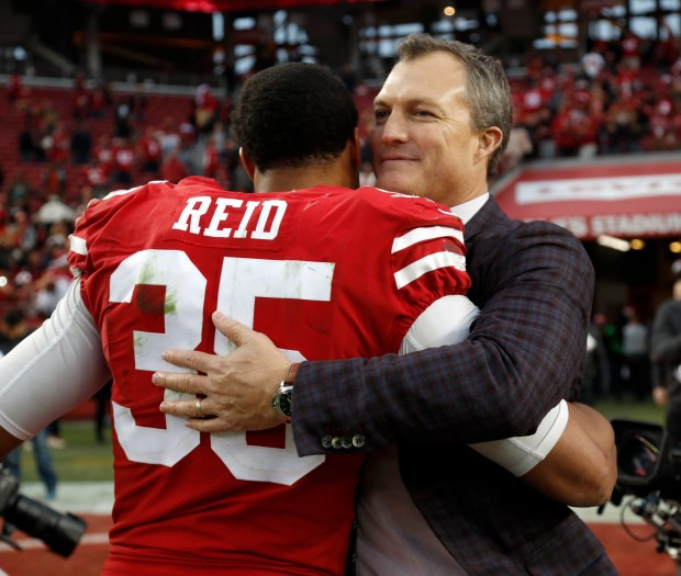 San Francisco 49ers general manager John Lynch hugs San Francisco 49ers' Eric Reid (35) after their 44-33 win against the Jacksonville Jaguars for their NFL game at Levi's Stadium in Santa Clara, Calif., on Sunday, Dec. 24, 2017. (Nhat V. Meyer/Bay Area News Group)